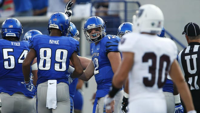 Memphis Tigers quarterback Paxton Lynch (12) celebrates with his teammates as Missouri State Bears safety Jared Beshore (30) looks on after a Tigers touchdown during the first quarter of the Bears' season opener game against the Memphis Tigers on Saturday at the Liberty Bowl Memorial Stadium in Memphis.