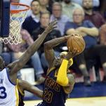 Cleveland Cavaliers forward LeBron James drives between Golden State Warriors guards Klay Thompson (left) and guard Stephen Curry (30) on Feb. 26 in Cleveland. It was the only time this season the Cavs faced the Warriors with a healthy LeBron. The NBA Finals begin Thursday night.