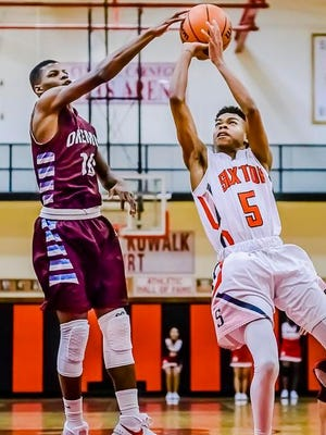 Chaz Richardson ,left, of Okemos blocks a shott attempt by Zhervonte Smith of Sexton during their game Tuesday January 12, 2016 in Lansing.
