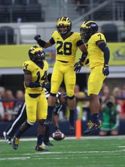 Michigan's Josh Metellus (14), Brandon Watson (28)
