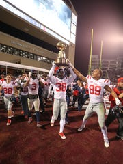 Ole Miss's Marquis Haynes (38) holds the Egg Bowl trophy above his head following the Rebels' 31-28 victory over Mississippi State Thursday in Starkville.
