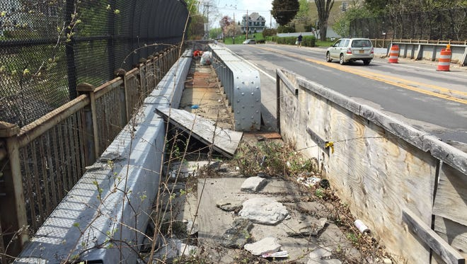 This sidewalk on the Carmel Avenue bridge in Brewster has been closed since 2010. Metal plates and wooden planks cover holes in the walkway, which runs above Metro-North Railroad's Harlem Line.