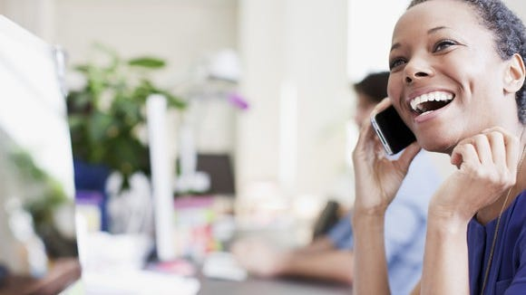 A woman smiling and talking on a smartphone.