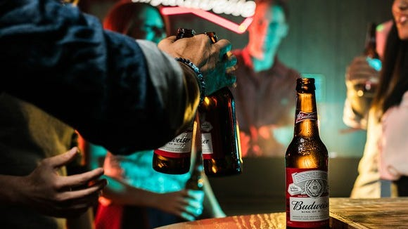 File photo of people drinking bottles of Budweiser beer in a bar.