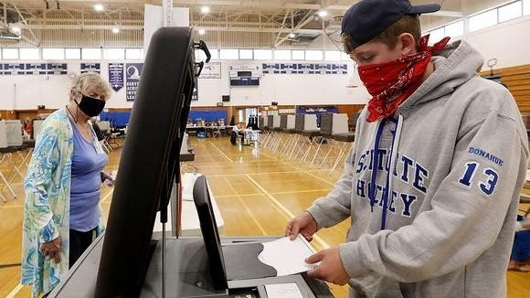 First time voter Christian Donahue, 18, casts his ballot while voting in Precinct 3 at Scituate High School on Sept. 1, 2020.