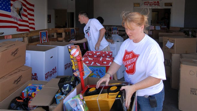 Salvation Army warehouse manager Kim Geise, right, and Capt. Joe Katz of the 25th Infantry Army from Schofield Barracks, sort through toy donations.