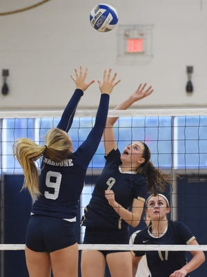 John Jay High School's Nicole Nardone, left, tries to block a hit from Our Lady of Lourdes' Grace Rappleyea, right, during an Oct. 4 match in Wiccopee.