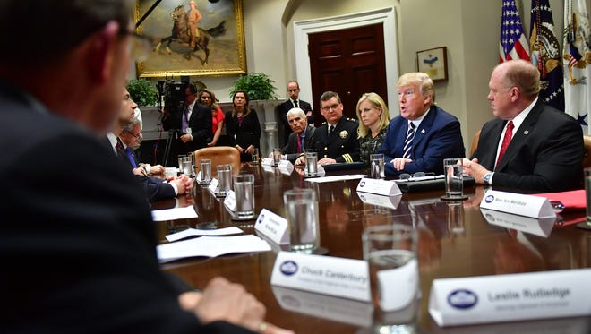 President Donald Trump and Larimer County Sheriff Justin Smith participate in a law enforcement roundtable on sanctuary cities at the White House on March 20.