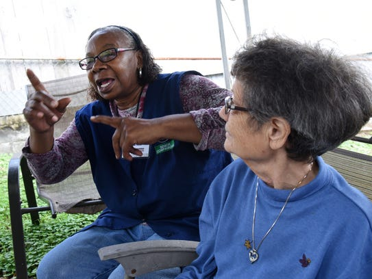 Senior Companion Ella Neal signs a story during a visit with her client Mary, who is deaf and has dementia, on Tuesday, Nov. 7, 2017. Mary is one of three seniors Neal serves through the volunteer program.