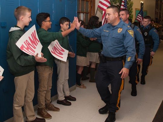 Newfield Police Chief, Edward Seibert, high fives student