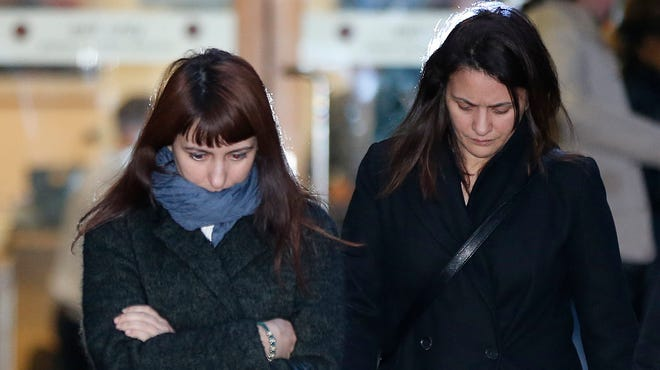 Italian sisters Francesca, left, and Elisabetta Grillo, former personal assistants to British TV chef Nigella Lawson and her ex-husband, art collector Charles Saatchi, leave the Isleworth Crown Court in west London on Nov. 27, where the sisters are on trial for fraud.