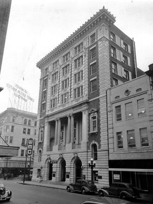 """The Goodwyn Institute Building at the corner of Third Street and Madison Avenue as it appears in the Spring of 1941.  It faces 75 feet on Madison and 117 feet on Third Street and was built by the well-known contractors Selden-Breck Construction Company of St. Louis and Memphis.  The building is seven stories high and has in addition a basement of 5,768 square feet.  The building is of steel skeleton or frame, which is enclosed in fireproof, hard burnt tile and the entire building is billed as """"absolutely fireproof.""""  The exterior walls are built of stone to the second floor, and from there up of """"Harvard Gate"""" brick and white terra cotta.  This """"Harvard Gate"""" brick was first used in some entrances, piers and adjacent walls on the campus of Harvard University.  The architectural style of the building is that of French Renaissance.  The grand lobby of the building is 45 feet wide and 50 feet deep and rises to a height of 50 feet.  Two eight- foot wide white Italian marble staircases adorn the lobby.  The building, which was made possible with funds from the will of William Adolphus Goodwyn (1824 - 1898), was formally opened and dedicated in 13 Sept 1907.  His will declared that the building be built and that it be used for free lectures and a free library.  It further stated that """"no part of the building is to be used for political gatherings, but when the lecture hall is not used otherwise it may be rented for musical concerts, art exhibitions or other purposed likely to elevate the public morals and taste."""""""