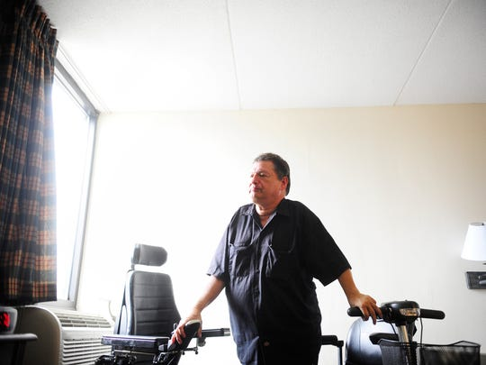 Emanuel Poznanski stands briefly in his room at the Motor Inn in New Oxford as he transfers himself from his scooter, right, to his power wheelchair on Friday, Aug. 17, 2012.