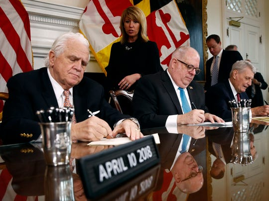 Maryland Gov. Larry Hogan, center, signs a series of bills between Senate President Thomas V. Mike Miller, left, and House Speaker Michael Busch during a ceremony in Annapolis, Md., Tuesday, April 10, 2018. The day after the state's 2018 legislative session wrapped up, Democrat and Republican state lawmakers highlighted bipartisan work in contrast to partisan gridlock in the nation's capital.