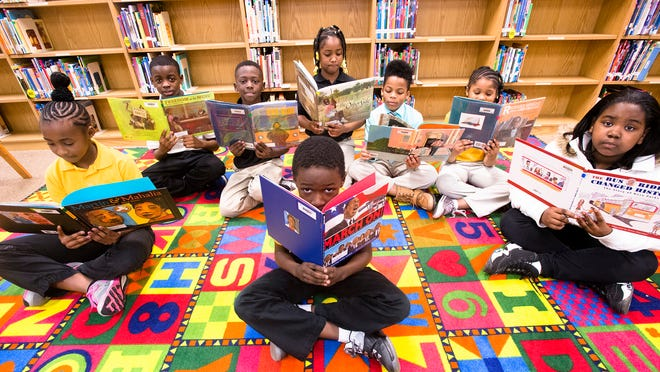 From back left, U'llyriah Lewis, 9, Cameron Haynesworth, 9, Keontaye Howard, 9, Jamil Young, 8, Nijel Payne, 9, Zaile Jennings, 8, Mikerria Warren, 9, front, and Jamarcus Howard, 9, hold up picture books used to teach them about civil rights history in the library at Seth Johnson Elementary School on Feb. 23.