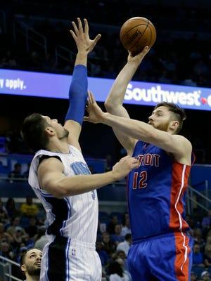 Detroit Pistons center Aron Baynes  shoots over Orlando Magic center Nikola Vucevic on Wednesday, April 6, 2016, in Orlando, Fla.