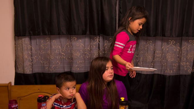 The Cuahua children, from left, Enrique, 5, Cecily, 10, and Marrissiah, 6, finish up their dinner before working on homework and getting ready for bed Tuesday evening. The kids are American citizens, but their father, Antonio Cuahua, was recently deported to Mexico, his country of origin, after a U.S. Immigration and Customs Enforcement (ICE) raid recently. The children are staying with their aunt, Jacqueline Linares of Owensboro, Ky., until they can obtain passports and then move to Mexico, a country they've never visited, to live with their father.
