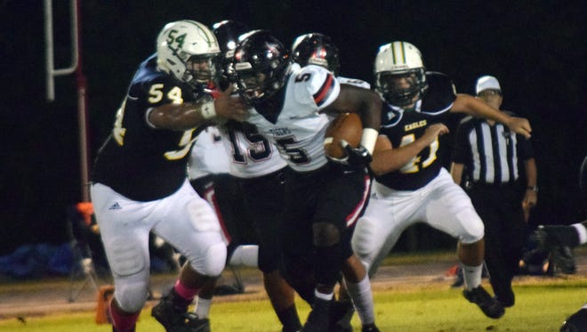 Many running back Ni'Kendrick Carter (5) breaks a tackle from Menard's Cody Crooks-Saucier Friday, Oct. 12, 2018 in a conference game at Menard. Many won 47-0.