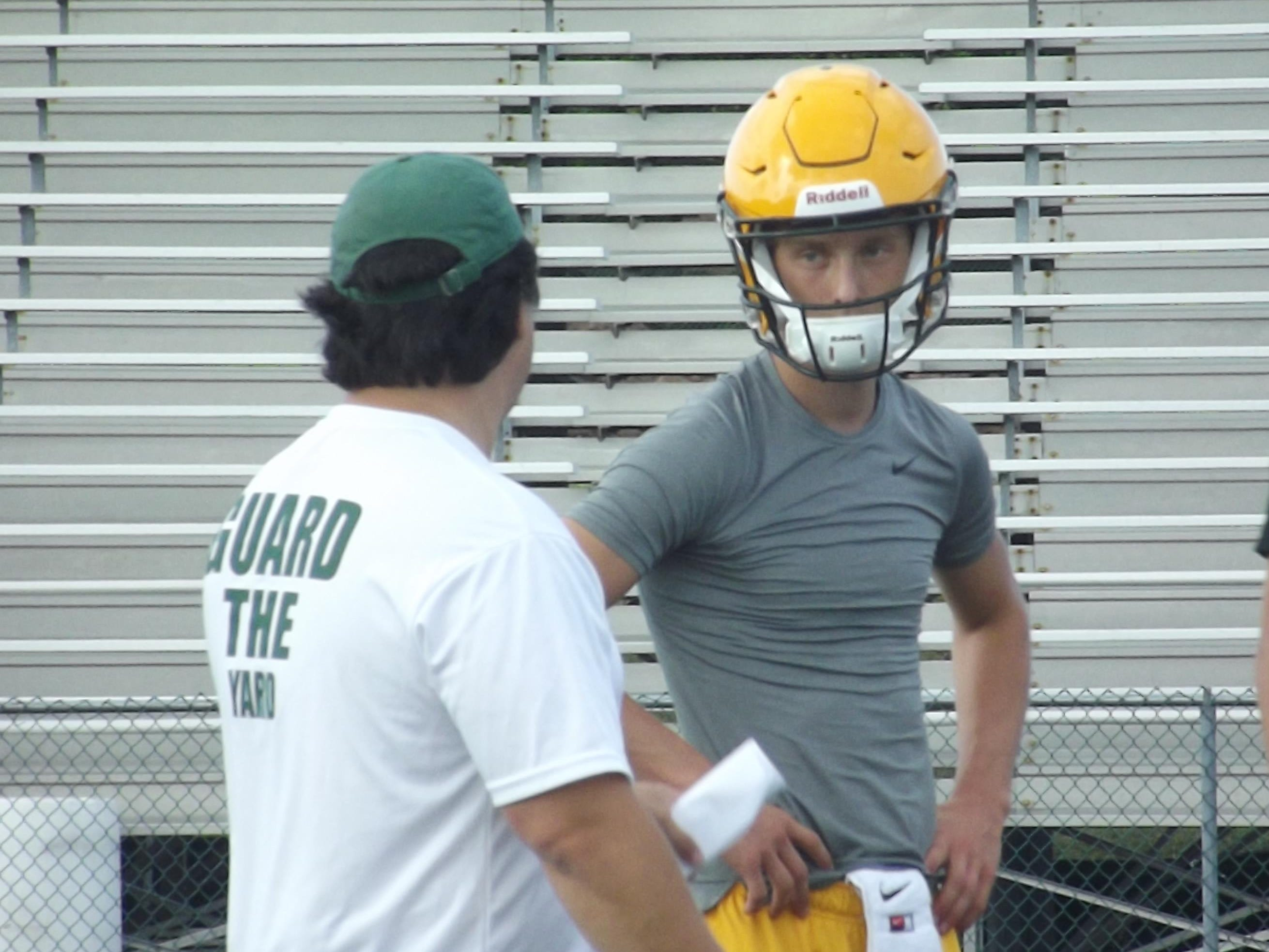 Senior Will Ark receives instruction from Ashwaubenon assistant coach Chad VanLaanen at practice Wednesday. Ark is expected to replace James Morgan as the team's starting quarterback.