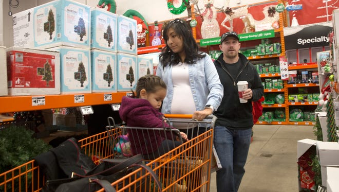 The Peterson family -- Richard, right, Vannan and their daughter Lily -- shop Friday at the Home Depot in Farmington.