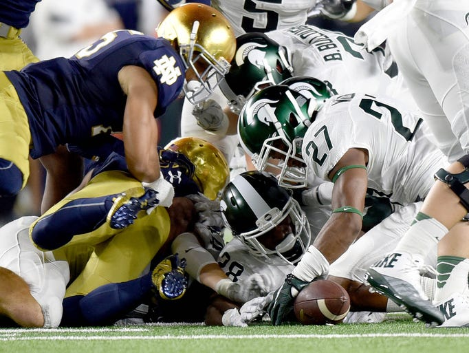 Michigan State players pounce on a punt mishandled