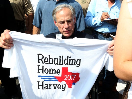 Texas Gov. Greg Abbott receives a t-shirt as a gift in Rockport on Thursday, September 21, 2017. He and George Strait were in town to visit with individuals affected by Hurricane Harvey.