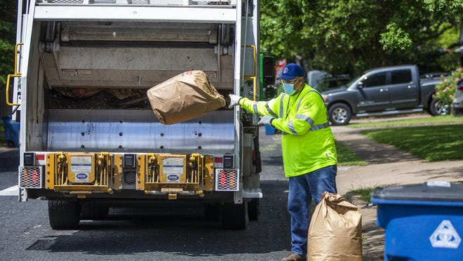Austin Resource Recovery employee Damien Bailey-Harris runs his routes in Northwest Austin as he picks up recyclable waste on May 27.