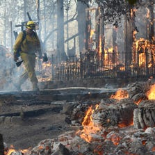 A firefighter walks past a burning structure on Cedar Drive in Oakhurst, Calif., Sunday, as two raging wildfires in the state forced hundreds of people to evacuate their homes.
