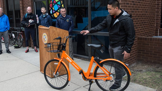 David Wong, City Launcer for Spin, talks about how the bicycles work in front of the Downtown Salisbury Parking Garage on Thursday, Feb. 22, 2018.