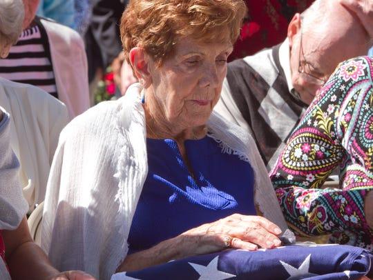 Melba Van Cuyl holds the American Flag folded in ceremonial