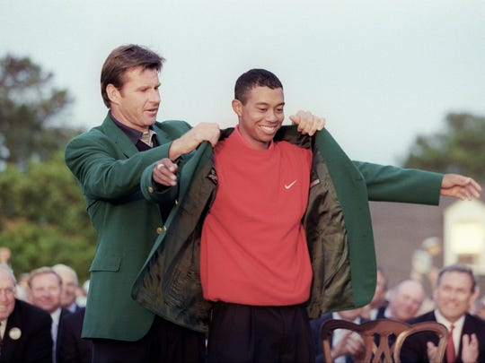 Tiger Woods receives green jacket from 1996 champion Nick Faldo after Woods won the 1997 Masters by shooting 18-under. (Timothy A. Clary, AFP/Getty Images)