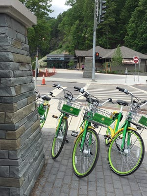 Green and yellow Lime bicycles are parked in front of Watkins Glen State Park waiting for users. The bike-rental program uses a mobile phone app.