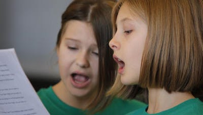 Left, Lexi Hall and Anna Coleman members of the Monfort Heights Elementary Fifth Grade Chorus, share sheet music duing a holiday concert at the Cincinnati Museum Center at Union Terminal last year