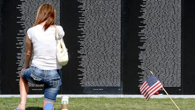 In this file photo, Stephanie Milner kneels before the thousands of names etched into the Traveling Vietnam Memorial Wall in Veterans Plaza of Northern Colorado at Spring Canyon Community Park.
