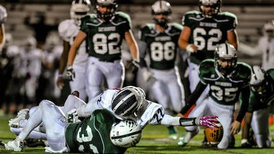 New Brunswick's Dylan Johnson stretches the ball toward the end zone in a game against East Brunswick last season.
