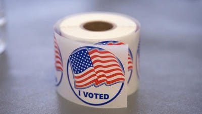 A roll of 'I Voted' stickers, which are handed out to residents after they vote, sit on an election officials table at a polling place on November 4, 2014