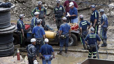 Rescue workers gather at the entrance to the Jellico Mine No 1. on Monday, June 20, 2011 in Middlesboro, Ky. Three mine maintenance workers were freed and appeared to be in good health Monday after being trapped for 14 hours in the flooded southeastern Kentucky mine.