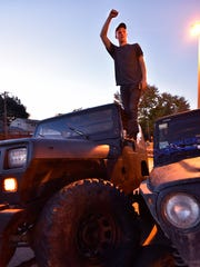 Matt Hinkle, of Garden City, is triumphant after successfully stacking his 1994 YJ model Jeep.