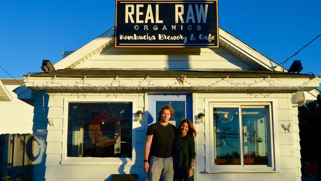 Logan Willey, owner of Real Raw Organics, is shown with her boyfriend in front of the shop.