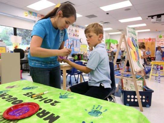 Kindergarten teacher Ellen Couch helps Alex Peyton