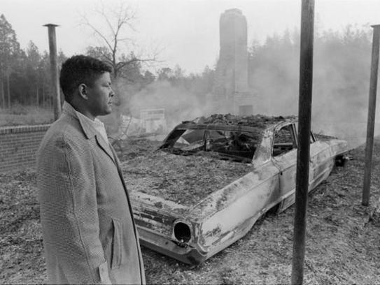 One of Vernon Dahmer's son looks at the burned home