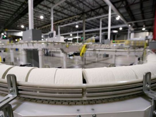 Rolls of toilet paper move along a conveyer Friday
