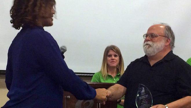 Venyke Harley, a loss control manager, presents an award to Greer Mayor Pro-Tem Wryley Bettis.