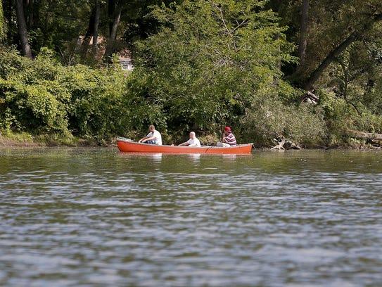 Three Fishermen paddle upstream on the Chemung River,