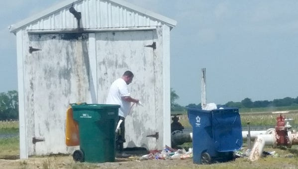 Michael B. Warncke cleans up trash that led to his arrest for illegal dumping by DNREC's Environmental Crimes Unit.