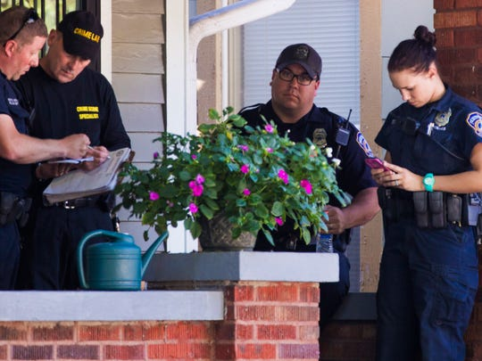 Crime Lab tech speaks with officers on the front porch of a home where a robbery suspect was shot early Monday evening.