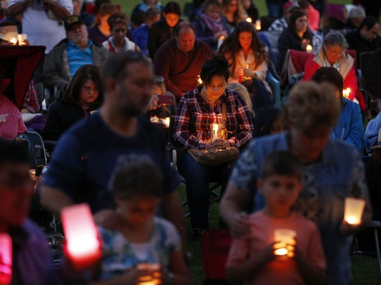 People bow their heads in prayer during a prayer vigil Saturday in Winston, Ore. The vigil was held in honor of the victims of the fatal shooting at Umpqua Community College last week.