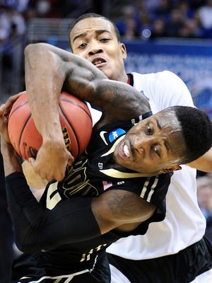 Purdue's Jon Octeus is fouled by Cincinnati's Troy Caupain, top, in the second round of the NCAA Tournament at the KFC Yum! Center in Louisville, Ky., on Thursday, March 19, 2015. Cincinnati advanced, 66-65, in overtime. (Wally Skalij/Los Angeles Times/TNS)