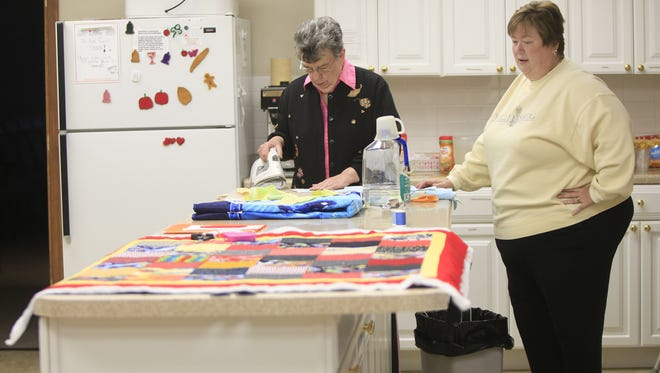 Darlene Cooper talks with Janet Throwbridge while they work on the quilts Monday afternoon in the kitchen of Yorktown Christian Church. Darlene Cooper talks with Jannet Throwbridge as she irons out materials for the knotting quilts the volunteers at the Yorktown Christian Church are making to pair with Reach ministries food backpacks that go to school children. The volunteers say they have seen the need for organizations like theirs to step up and help others in the community.