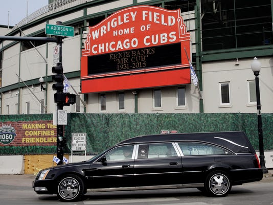 """The hearse carrying the casket of Hall of Fame slugger Ernie Banks drives around the Wrigley Field after the memorial service at Fourth Presbyterian Church in Chicago on Saturday, Jan. 31, 2015. Banks died Friday at 83 after a heart attack, according to an attorney representing his family. Known as """"Mr. Cub,"""" Banks is remembered as much for his boundless enthusiasm despite playing on mostly losing teams as his 512 home runs and two MVP awards. (AP Photo/Nam Y. Huh)"""
